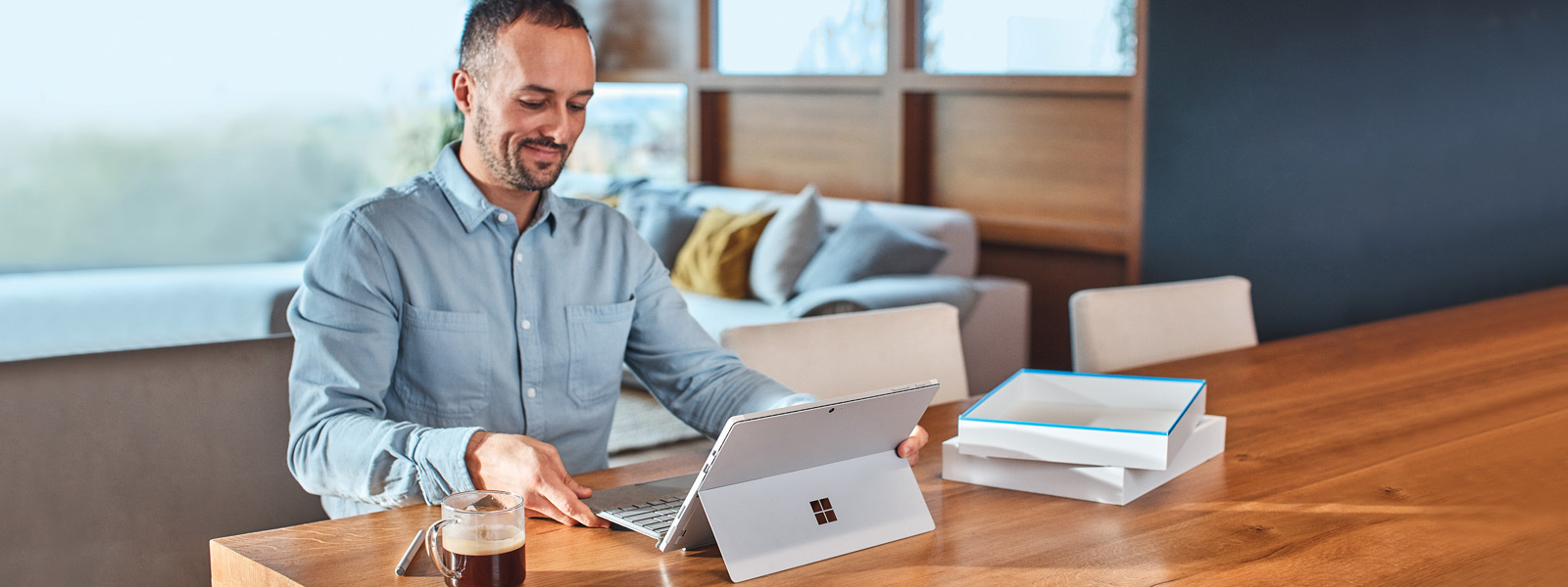 Man sitting at a table with a Surface laptop and a cup of coffee