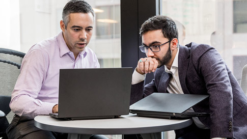 Two men looking at a laptop while sitting at a table