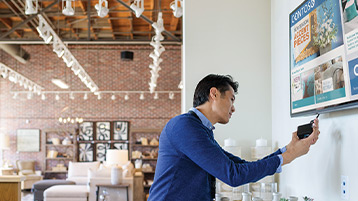 Male employee in commercial retail store plugging Xogo IoT device into wall-mounted monitor. The screen shows product promo ads for home furnishings. A desktop monitor sitting on a desk behind him displays the Windows 10 log in page