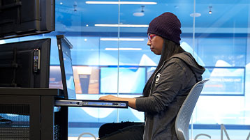 Woman in a stocking hat and hooded sweatshirt working on a network server station inside a secure room