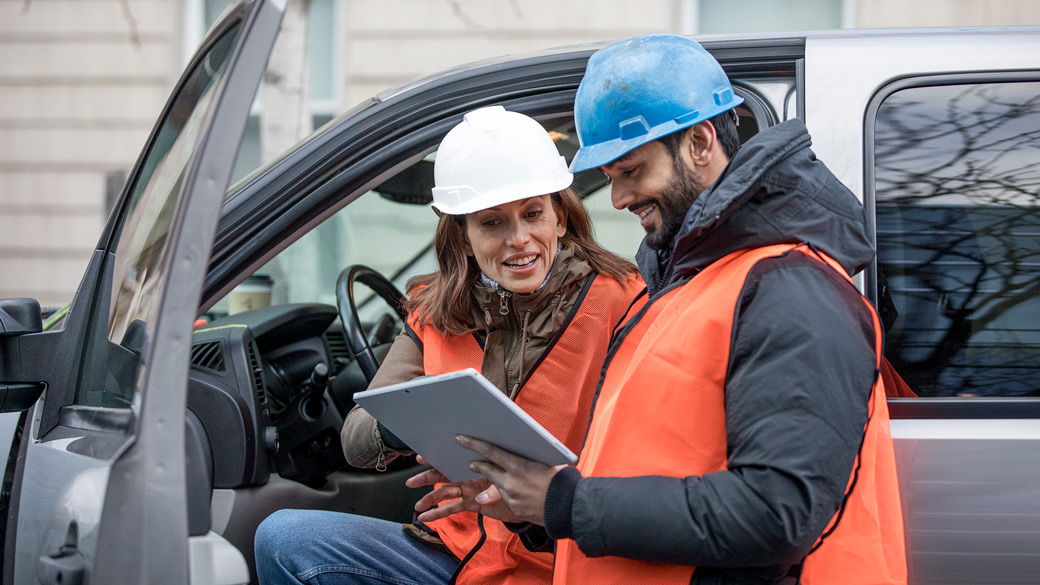 Man and woman wearing orange vests and hard hats review a tablet