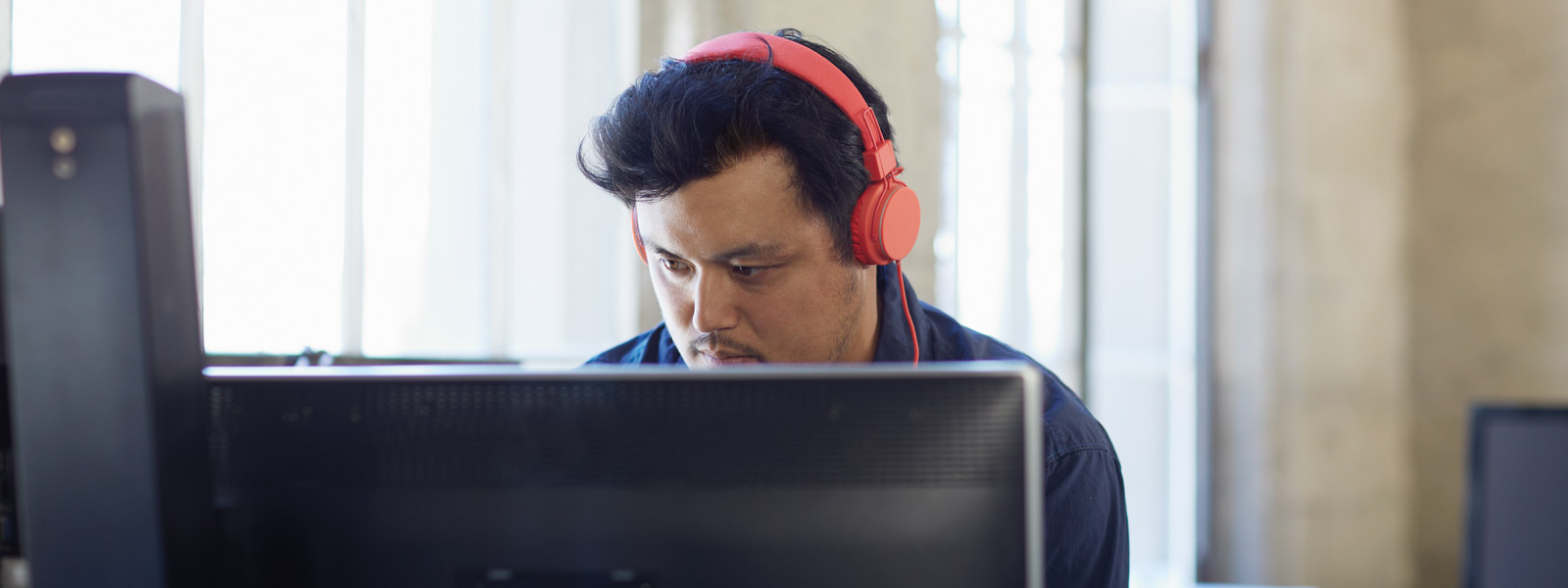 Man with red headphones sits at computer working