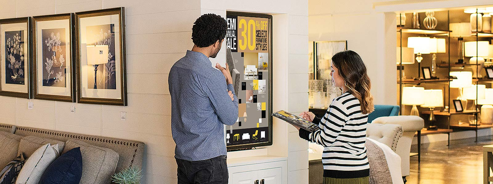 Man and woman review digital signs in retail store