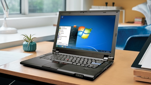 Laptop on table showing Windows 7 on screen