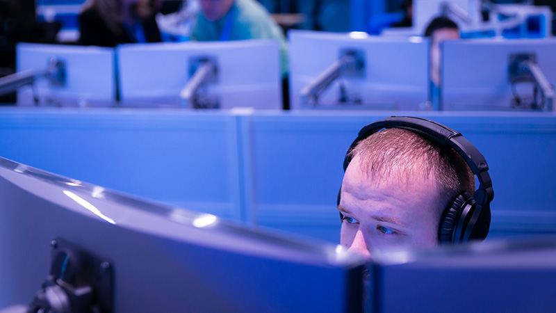 Man with headset sitting in front of dual monitor desktop