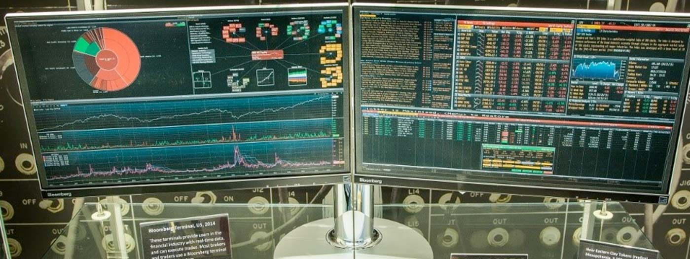 Two monitors with banking graphs on them