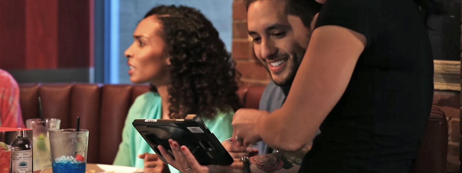 Customers interacting with payment device at table