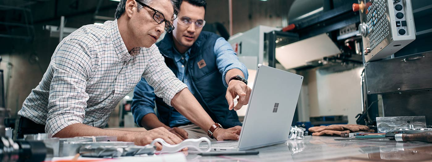 Two professionals interacting with Surface Book