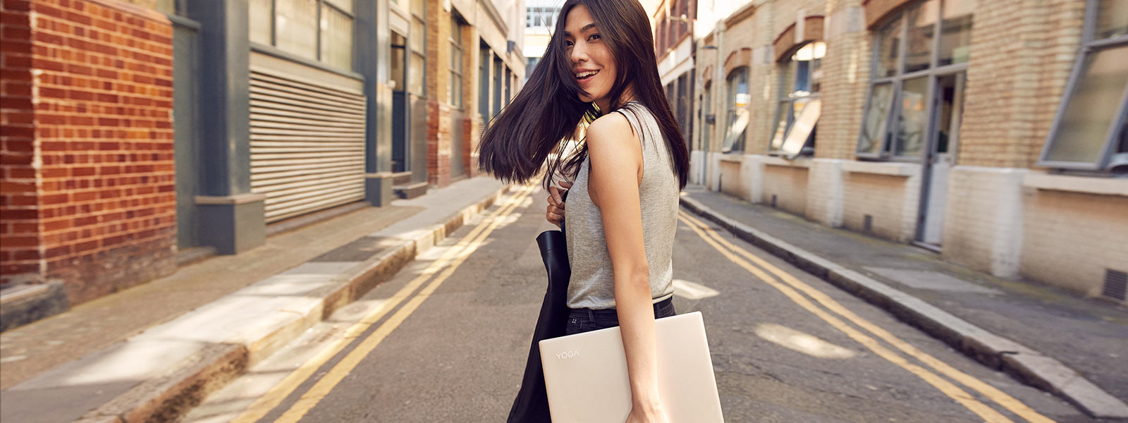 Woman walking down street with Lenovo YOGA 910