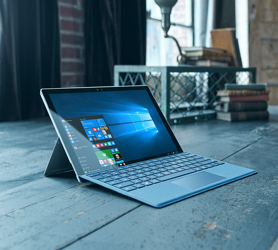 Surface Pro 4 on wooden floor with Windows 10 start menu open on screen