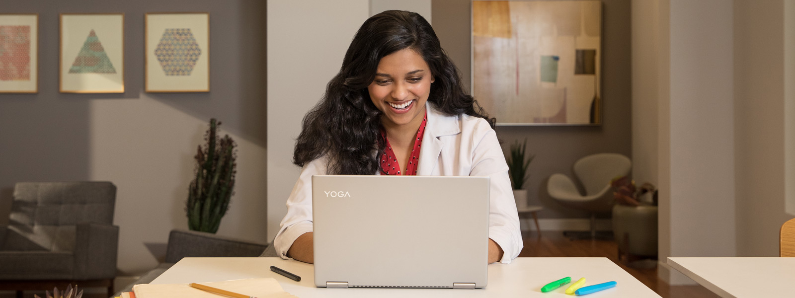 Smiling student using a Windows 10 laptop while sitting at a desk
