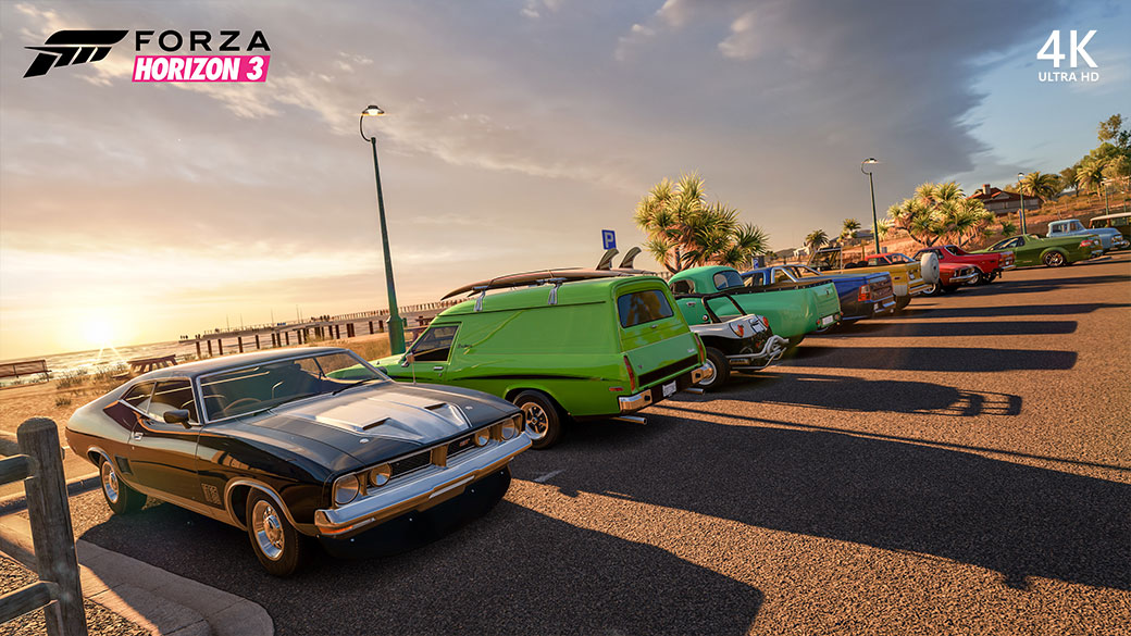 Gameplay image of Forza Horizon 3 with cars parked at a beach at sunset
