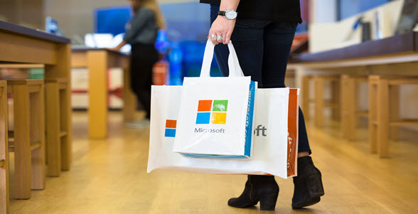 Customer walking out of store with Microsoft shopping bags