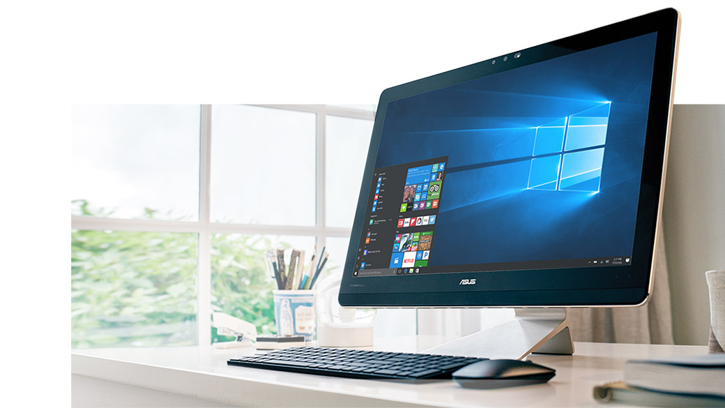 Desktop PC on desk with mouse and keyboard displaying Windows 10 start menu on screen