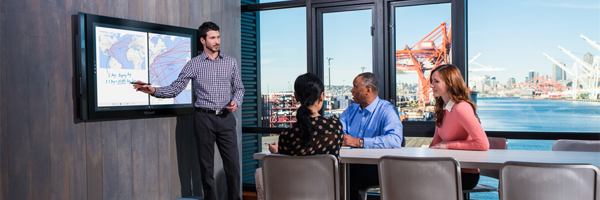A designer and business manager discuss a new design on a Surface Hub