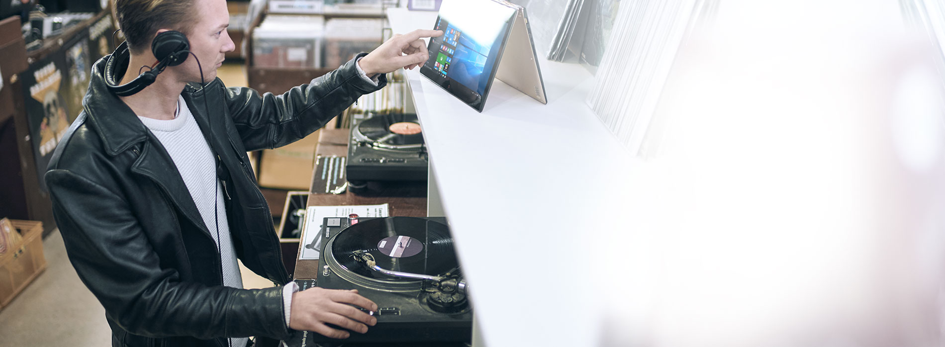 Man wearing headphones playing vinyl records in record store while touching the screen ofa 2-in-one device placed on a shelf at eye level