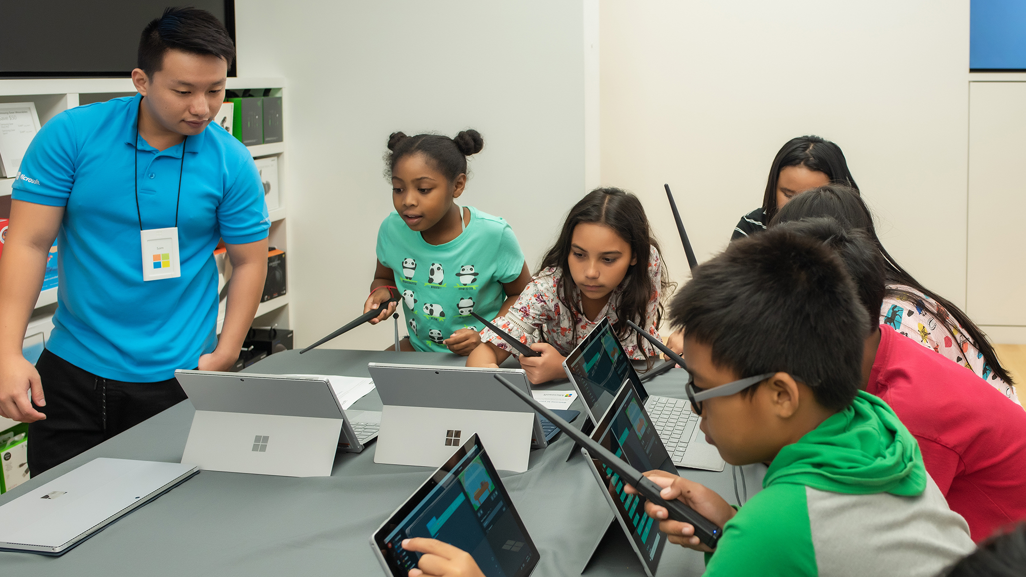 Microsoft employee instructs students how to code using the Harry Potter Kano coding wand and a Surface device.