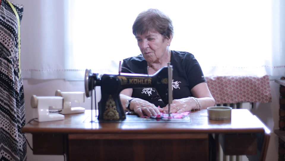 Play Video, A woman guiding a piece of fabric through a sewing machine.