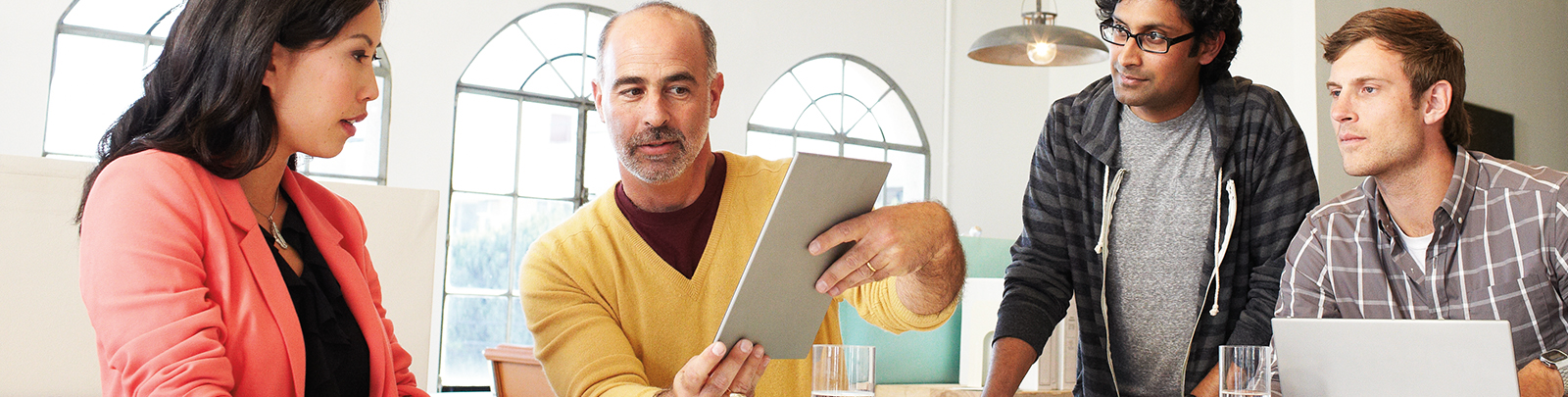 A man is showing his tablet to his colleagues.