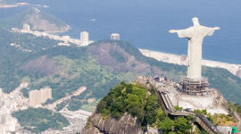 Aerial photo looking down on the city Rio de Janiero with Cristo Redentor statue in the foreground.