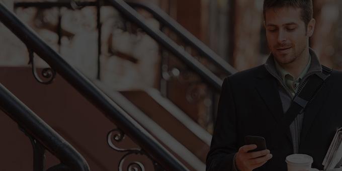 A man holding a smartphone, using Office 365 Enterprise E1.