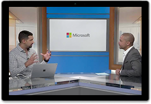 Video still from the webcast Microsoft 365 Enterprise: Empower your employees of two people sitting at a table talking