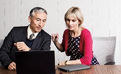 man and woman look at laptop