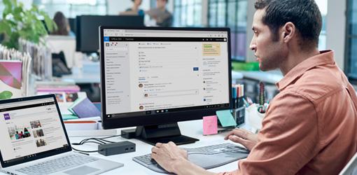 Un hombre mirando un monitor de escritorio que ejecuta SharePoint