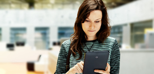 Una mujer mirando la pantalla de una tableta; más información sobre Exchange Server 2016
