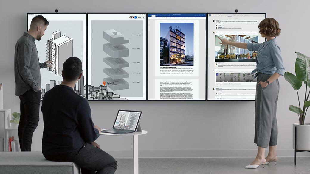 Dos hombres y una mujer en una reunión, con cuatro dispositivos Surface Hub 2 en forma de mosaico montados en la pared