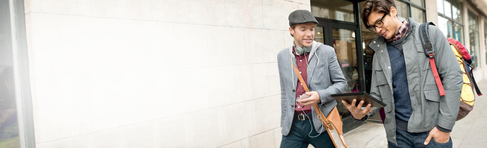 Dos hombres caminando por la calle y utilizando Office 365 en una tableta.