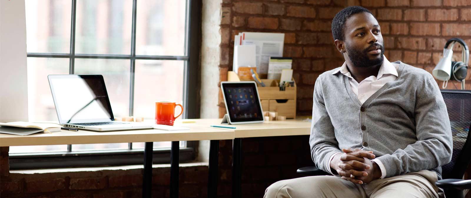 Hombre sentado junto a un escritorio, y tableta y portátil con Office 365 Empresa Premium.