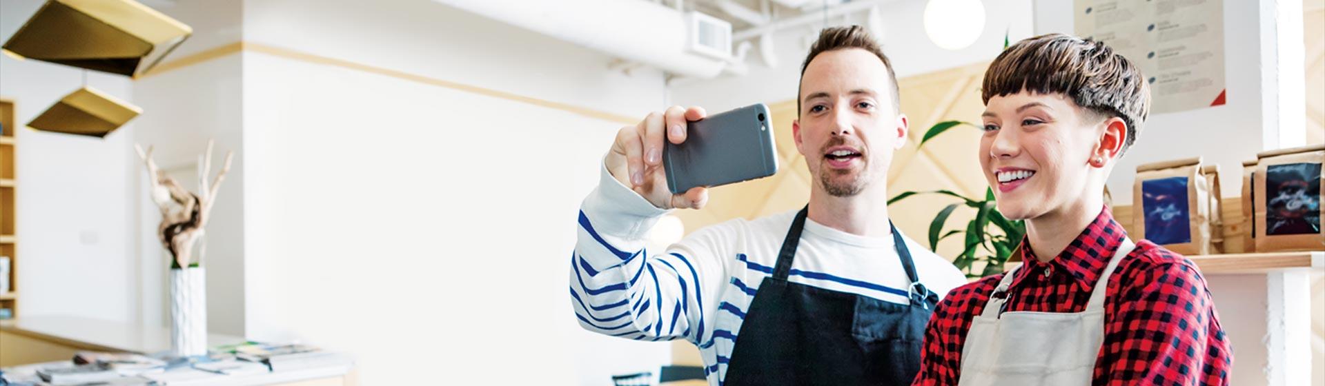 Dos personas sonriendo mirando un smartphone mientras usan Llamada RTC en Skype Empresarial