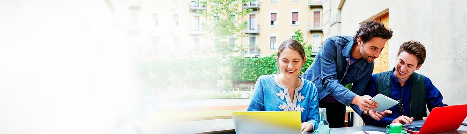 Una mujer y dos hombres trabajando juntos con equipos portátiles y una tableta en un café al aire libre.