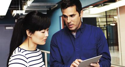 Un hombre y una mujer utilizando Office 365 en una tableta para trabajar en equipo.