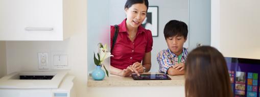 Una mujer y un hijo registrándose en el escritorio de una recepción de una consulta médica.