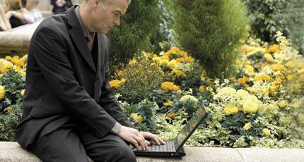 Hombre sentado fuera utilizando Office 365 en su portátil.