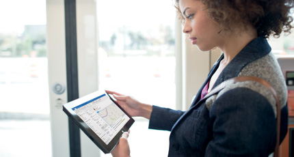 Mujer de pie en una oficina, utilizando Office 365 en una tableta.
