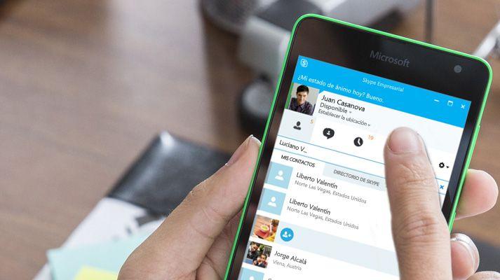 Una mano sostiene un dispositivo móvil con Skype para hacer una llamada