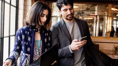 Dos personas en una oficina atendiendo una llamada de conferencia en un dispositivo móvil