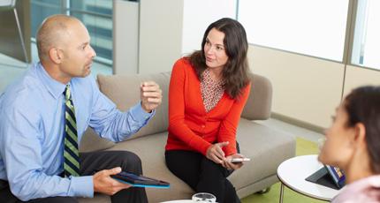 Dos personas sentadas en un sofá y otra sentada en una silla colaborando y usando una tableta y un teléfono.