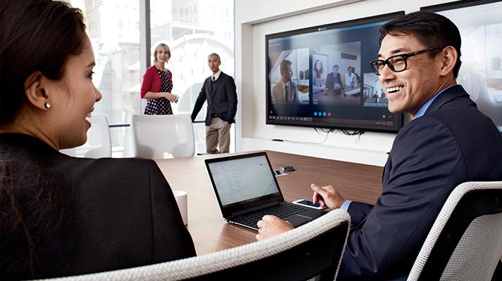 Varias personas reunidas y hablando en una sala de conferencias con asistentes a la reunión remotos que aparecen en una pantalla