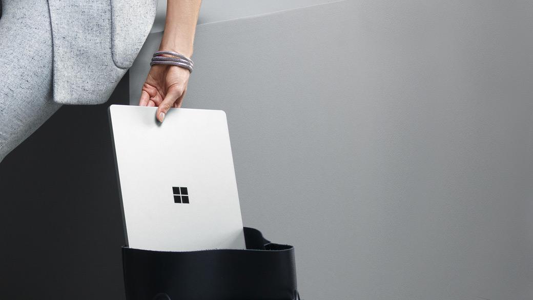 Una mujer saca del bolso un Surface Laptop plateado.