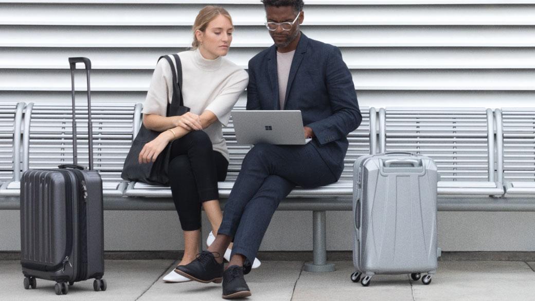 Una mujer y un hombre con dos maletas están sentados en un banco y trabajan con un Surface Laptop plateado.