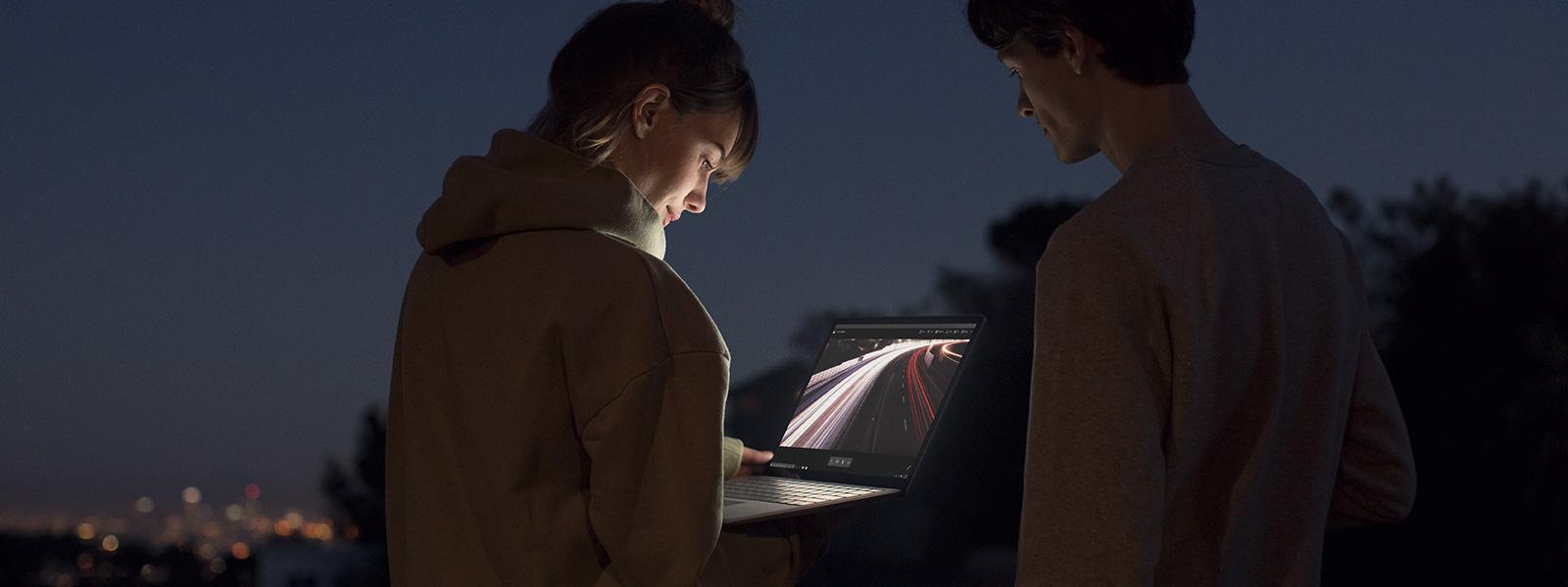 Imagen de dos estudiantes que miran Surface L por la noche.