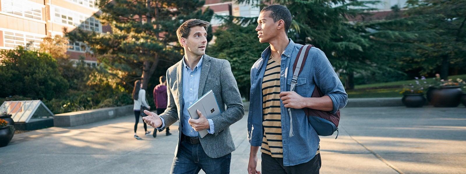 Profesor con estudiantes que transportan dispositivos de Microsoft