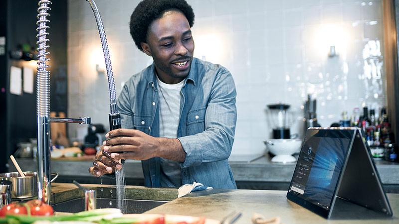 Hombre mirando a Cortana en un dispositivo 2 en 1 con Cortana en pantalla mientras corre agua en el fregadero de la cocina