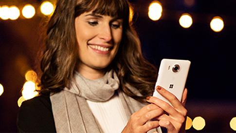 Mujeres mirando un teléfono con Windows 10