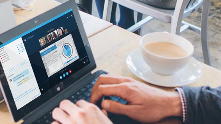 Usuario escribiendo en una tableta Surface con una reunión de Internet de Skype Empresarial en la pantalla