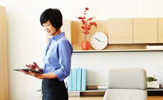Una mujer que trabaja en una oficina con una tableta y utiliza Office Profesional Plus 2013.